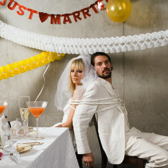 Newlywed Couple Tied up at Wedding Reception --- Image by © Ragnar Schmuck/Corbis